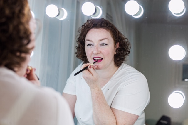 Top 5 makeup tips for London mums - woman putting on lipstick in mirror