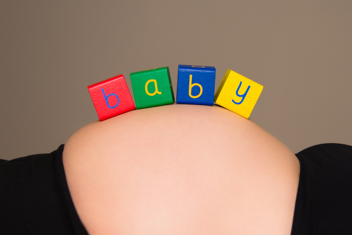 Baby in blocks sitting on mother's bump