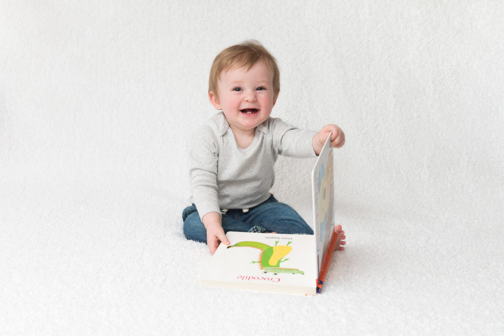 6-month old baby sits reading his book at photoshoot in Rotherhiithe, SE London
