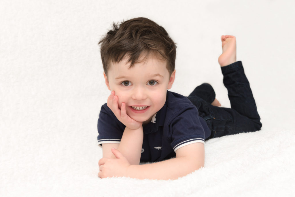 London child photoshoot in Notting Hill - boy posing on tummy on bed