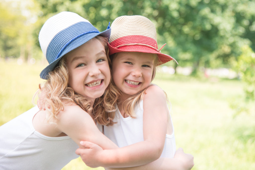 Smiling sisters in hats taken at a child photography session on Clapham Common by South London photographer