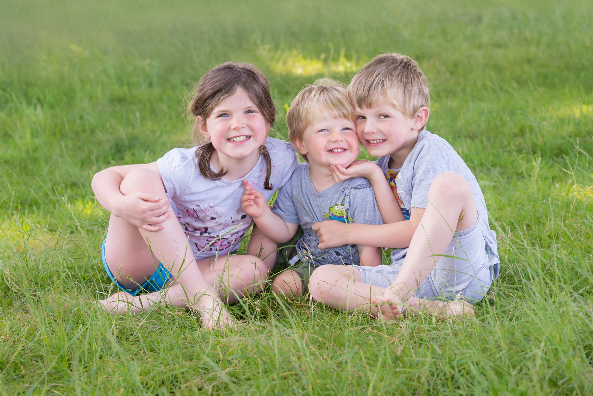 Photo of three children hugging on the grass in East Dulwich, South London