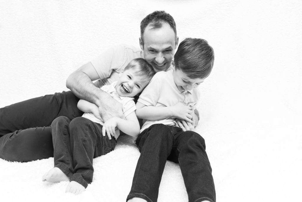 Family photography in Chelsea, London - black and white picture of dad laughing with his two boys