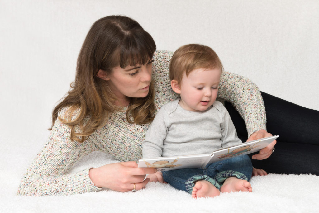 Mum sits reading book with her one-year old baby at family photography session in Croydon, South London