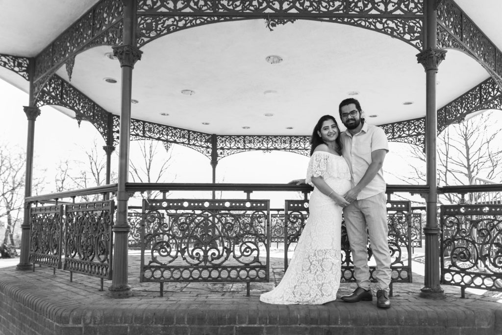Black and white image of pregnant couple posing by bandstand in Hampstead Heath taken by London pregnancy & maternity photographer