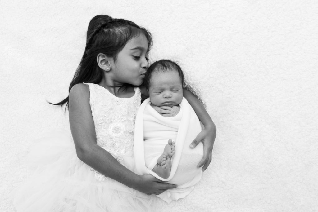 Girl posing with her baby sister at a professional newborn photography session in Westminster, London