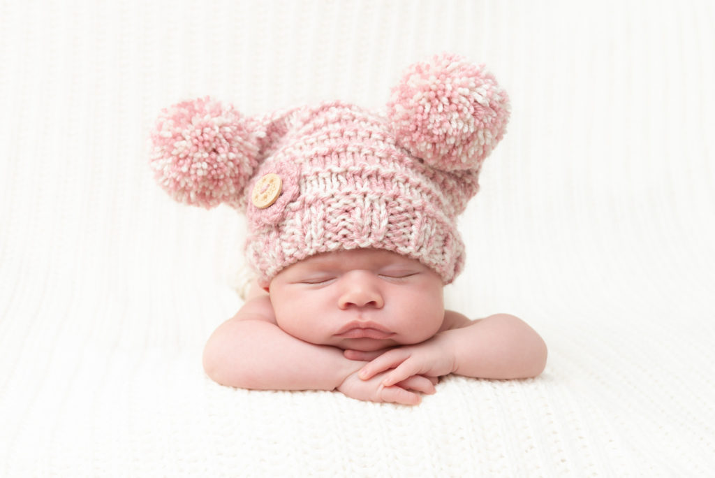 Baby on tummy in pink bobble hat in Surrey Quays at South London newborn photoshoot