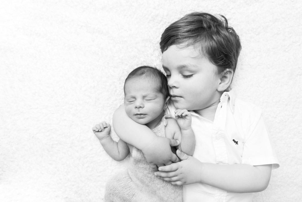 Black and white image of boy cuddling newborn baby brother taken at South London photography session