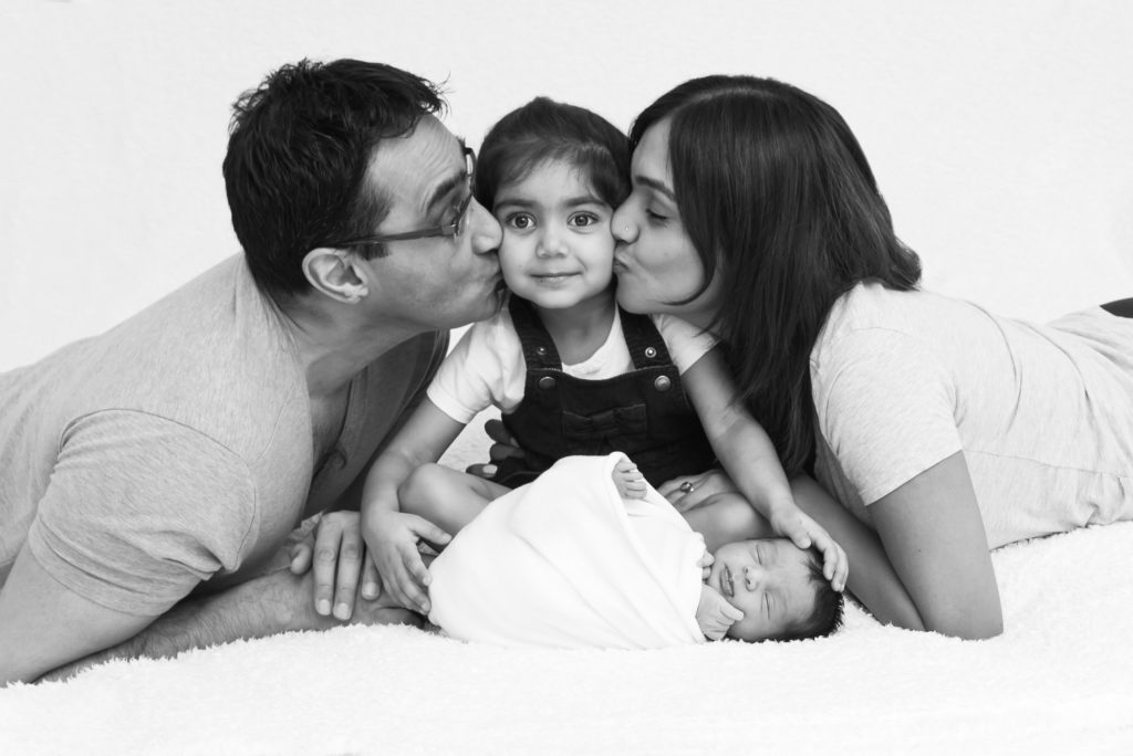 Black and white image of parents kissing child with newborn baby by South London family photographer