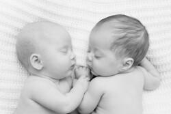 Black and white photo of twin newborns cuddling
